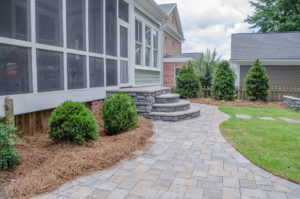 Seamless transition from screened porch to patio in outdoor living space