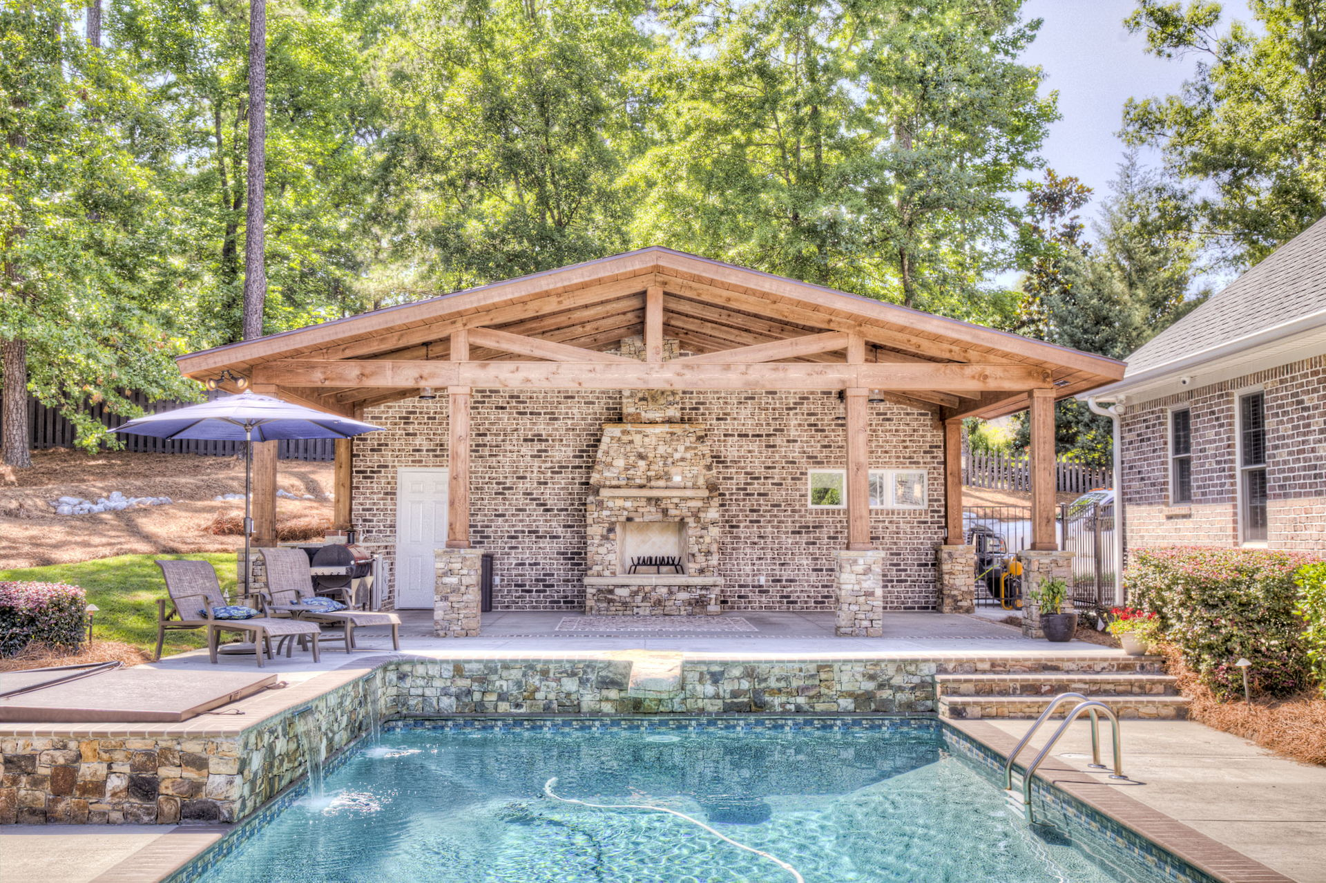 Poolscape and outdoor fireplace design in Augusta, GA
